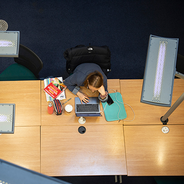 Student studying in library with laptop