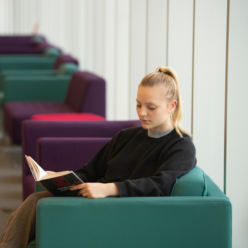 Student sitting on a chair reading a book