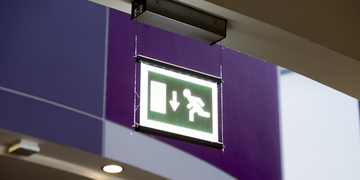 Green fire exit sign hanging from ceiling