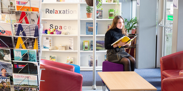 student reading a book in the libary